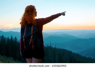 A relaxed red-haired woman in a dress is standing on top of a high mountain against the backdrop of a large mountain and spinning with happiness, raising her hands up. Bright sunset on the mountains