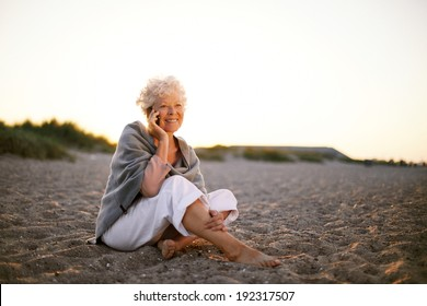 Relaxed retired woman wearing shawl sitting on sandy beach making a phone call. Old caucasian woman sitting on the beach looking at camera outdoors