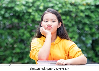 Relaxed schoolgirl primary student making pucker up face and resting her chin in her hand with colorful notebooks