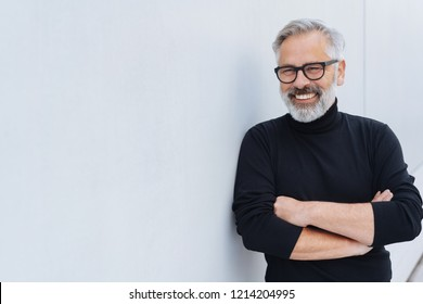 Relaxed self-assured senior man with beard and glasses standing with folded arms in front of a receding white wall