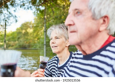 Relaxed senior citizen retired couple at the lake drinking a glass of red wine together