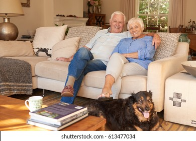 Relaxed senior couple sitting together on their vintage looking living room couch with the family dog at their feet