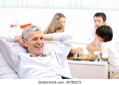 Relaxed senior man on sofa, family in background