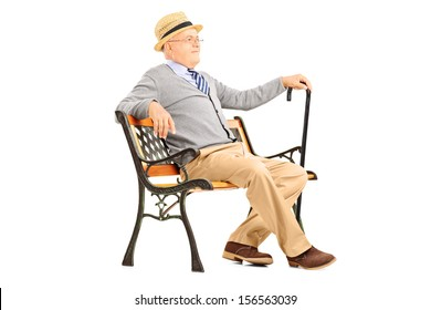Relaxed senior man sitting on a wooden bench and thinking isolated on white background