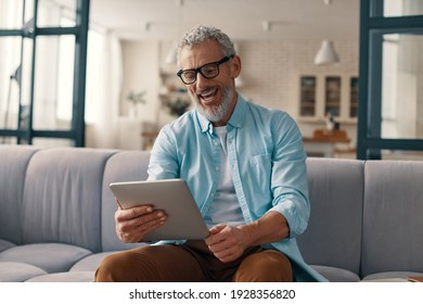 Relaxed senior man using digital tablet and smiling while sitting on the sofa at home