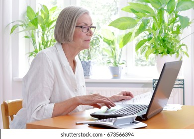 Relaxed senior woman at home with a calculator and lots of receipts in front of her laptop making her annual tax declaration
