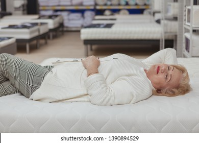 Relaxed senior woman trying orthopedic mattress on sale at furniture store. happy elderly female customer smiling with her eyes closed, lying on a new bed at home department shop