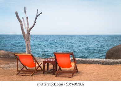 A relaxed set of 2 orange beach chairs sets by the beach in Ko Tao, Thailand.