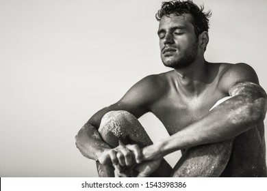 Relaxed sexy topless male model sitting on the beach with eyes closed. Black and White.