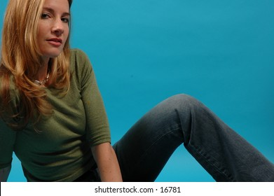 Relaxed shot of a beautiful, thin model in green top and jeans
