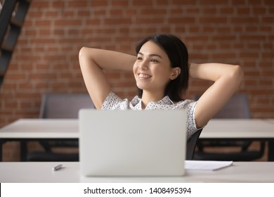 Relaxed smiling asian business woman take break to rest from computer at workplace holding hands behind head satisfied finished work, happy calm japanese employee feel no stress free in quiet office