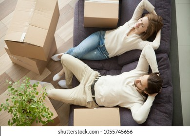 Relaxed smiling couple resting on couch moved in new home with boxes, happy real estate renters owners relaxing on sofa in living room, easy relocation with moving delivery service concept, top view