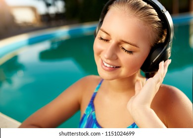 Relaxed smiling woman listening to music in headphones bathing in swimming pool. Blonde girl enjoys favourite song with goosebumps on skin. Waterproof headphones with touch control mobility concept.