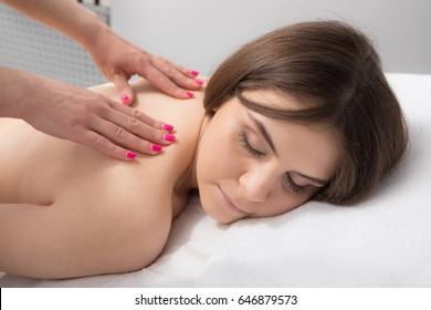 Relaxed smiling woman receiving a back massage