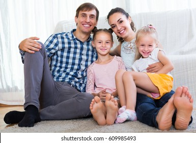Relaxed smiling young family of four posing in domestic interior