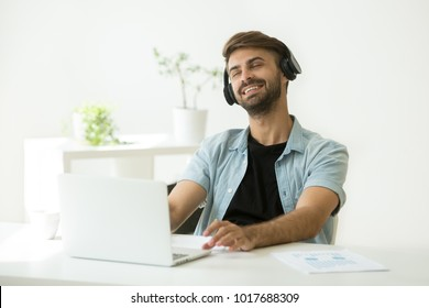 Relaxed smiling young man in headphones enjoying good music on laptop with eyes closed, happy casual office worker or student wearing headset listening to new audio tracks for relaxation at work home