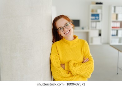 Relaxed smiling young woman in glasses standing in a colorful yellow sweater with folded arms leaning on a pillar in an office with copy space