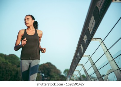 Relaxed sportswoman running outdoors alone on summer day by the banister