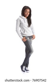 Relaxed standing pose from beautiful young black teenage girl, wearing grey hoodie sweater and blue jeans. Girl has long hair.