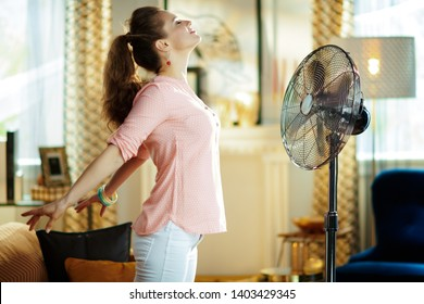relaxed stylish housewife at modern home in sunny hot summer day enjoying freshness in the front of working fan.