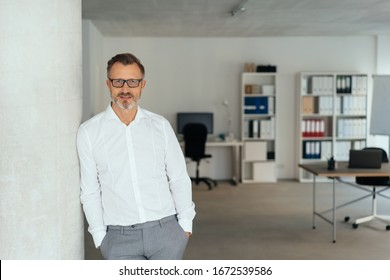 Relaxed successful businessman standing leaning nonchalantly against a wall with hands in pockets in a spacious office