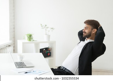 Relaxed successful businessman in suit enjoying office break holding hands behind head at workplace, calm happy ceo meditating or relaxing breathing air with eyes closed feeling no stress at work