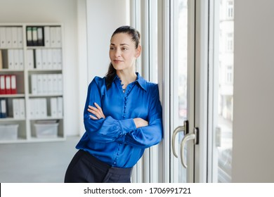 Relaxed successful young businesswoman standing watching as she leans nonchalantly against an office door