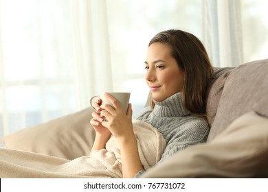 relaxed tenant resting holding a coffee mug sitting on a sofa in the living room in a house interior