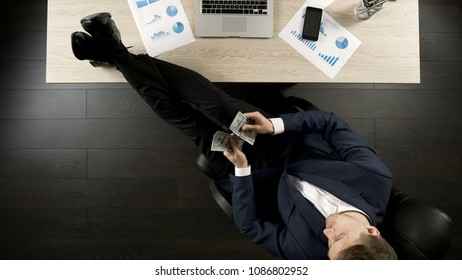 Relaxed wealthy businessman counting money, sitting with feet on table, top view