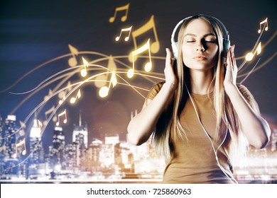 Relaxed white woman listening to music on night city background. Hobby concept