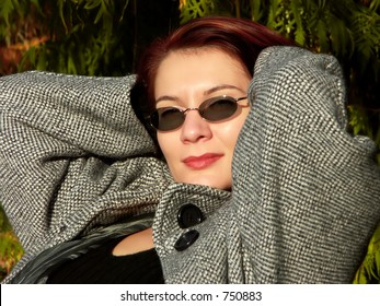 relaxed woman with arms behind head and a sexy look, sitting in the sun light in a park