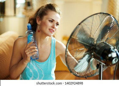 relaxed woman with bottle of cold water enjoying fresh air in the front of working fan at modern home in sunny hot summer day.