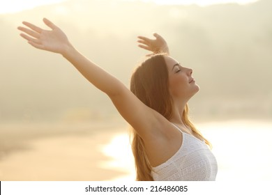Relaxed woman breathing fresh air raising arms at sunrise with a warmth golden background