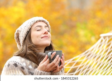 Relaxed woman breaths fresh air holding coffee cup for breakfast sitting on a rope hammock in autumn in a forest