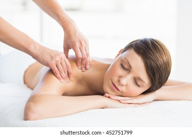 Relaxed woman enjoying back massage from masseur at spa