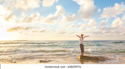 Relaxed woman enjoying sun, freedom and life an beautiful beach in sunset. Young lady feeling free, relaxed and happy. Concept of vacations, freedom, happiness, enjoyment and well being.