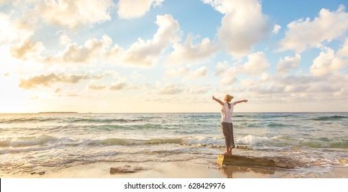 日の光と自由と生活を楽しむリラックスした女性、夕暮れの美しいビーチ。気楽でリラックスして幸せな若い女性。休暇、自由、幸せ、楽しみ、幸せのコンセプト。