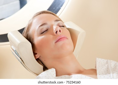 A relaxed woman with eyes closed ready for a CT scan