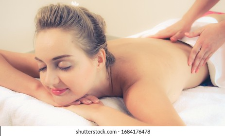 Relaxed woman getting back massage in luxury spa with professional massage therapist. Wellness, healing and relaxation concept.