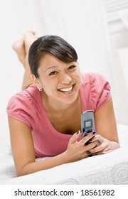Relaxed woman laying on bed and text messaging on cell phone