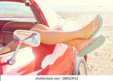 Relaxed woman legs and flip flops in a car window on the beach