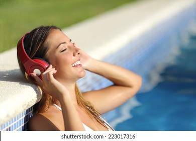 Relaxed woman listening to the music with headphones bathing in a pool