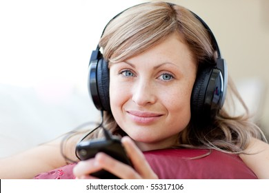 Relaxed woman is listening the music in the living-room at home