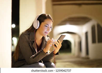 Relaxed woman listening to music from a smart phone sitting in the street in the night