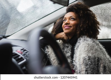 Relaxed woman looking the rain fall from inside a car during winter roadtrip.
