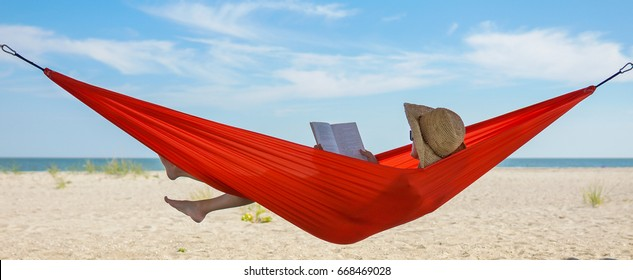 Relaxed woman lying in a hammock and reading a book on a sunny beach by the ocean