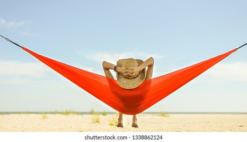 Relaxed woman lying in a hammock with the view of blue sky and sea line