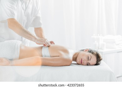 Relaxed woman lying in light interior during professional massage