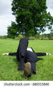 relaxed woman lying on the green grass with tree in the background