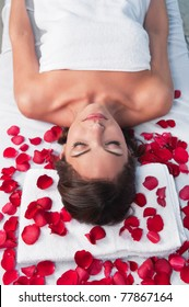 Relaxed woman lying on a massage table in a spa center with rose petals around